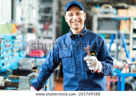 Auto mechanic smiling in his garage - stock photo