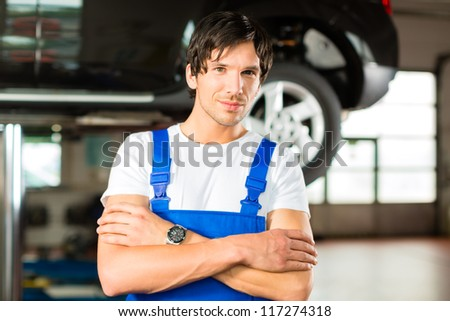 Auto mechanic standing in his workshop in front of a car on a hoist - stock photo