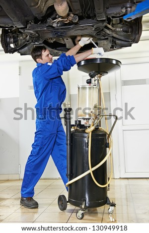 auto mechanic technician replacing and changing motor oil in automobile engine at maintenance repair service station - stock photo