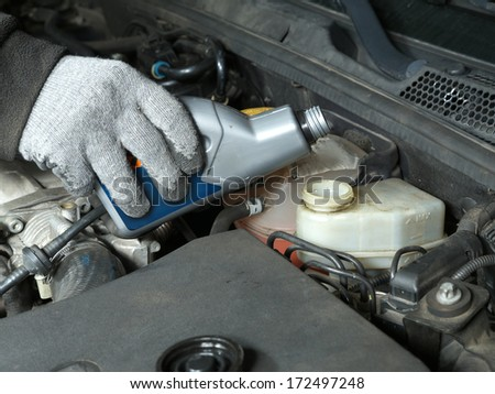 Auto mechanic topping up brake fluid in the vehicle - stock photo