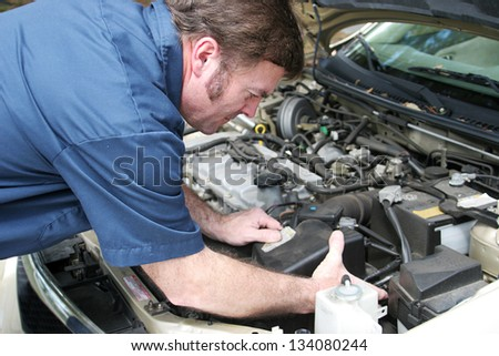 Auto mechanic under the hood, working on a car engine. - stock photo