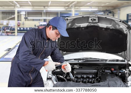 Auto mechanic use tool operation repaired engine at maintenance repair service station  - stock photo