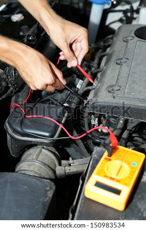 Auto mechanic uses multimeter voltmeter to check voltage level in car battery - stock photo