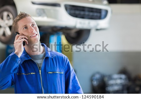 Auto mechanic using mobile phone in workshop - stock photo