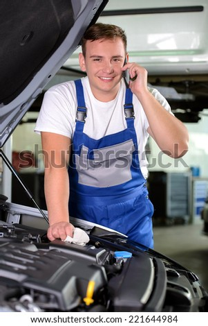 Auto mechanic using mobile phone in workshop, at car