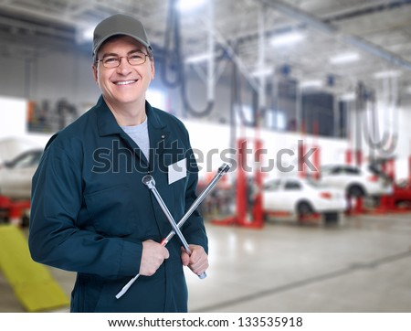 Auto mechanic with a wheel wrench in a workshop. - stock photo