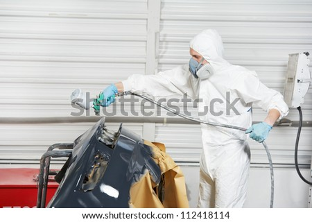auto mechanic worker painting car bumper at automobile repair and renew service station shop by spraing black color paint - stock photo