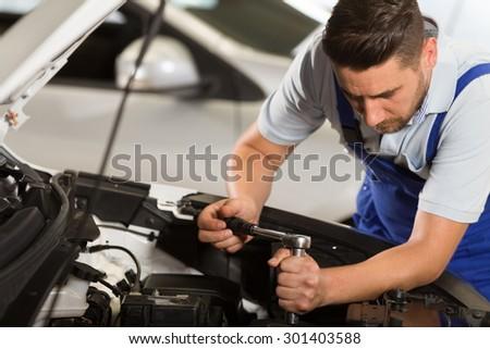 Auto mechanic working in repair shop. - stock photo