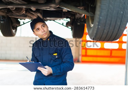 Auto mechanic working on a car in his garage