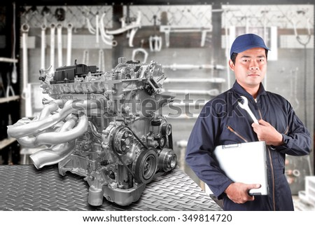 Auto mechanics holding a computer and tool for repair engine car at repair shop - stock photo