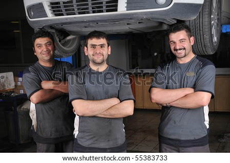 Auto mechanics smiling in car service - a series of MECHANIC related images. - stock photo