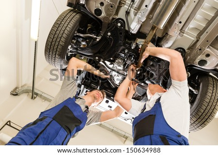 Auto mechanics working underneath a lifted car - stock photo