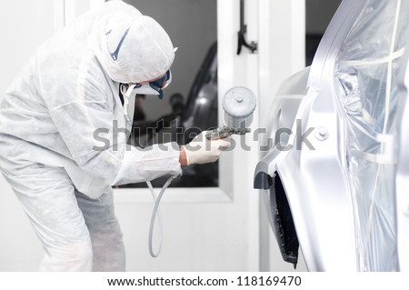 Auto painter spraying paint on a car body