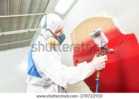auto painting worker. red car in a paint chamber during repair work - stock photo