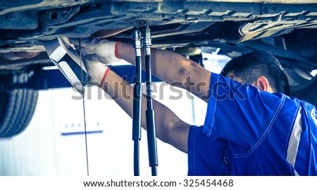 Auto repair factory parked engine,Workers concentrate on work. - stock photo