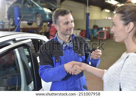 Auto repair mechanic giving car keys back to customer