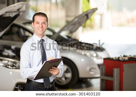 Auto repair shop manager posing at camera. - stock photo