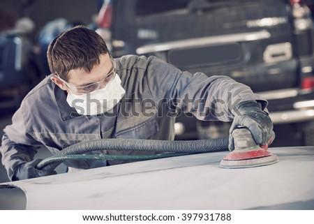 auto repairman grinding autobody bonnet  - stock photo