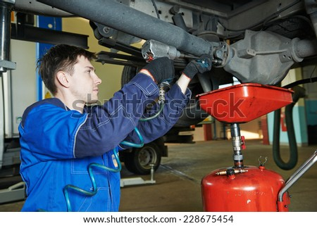 auto repairman mechanic disassembling axle reduction gear with wrench in car auto repair or maintenance shop service station