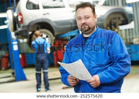 auto repairman mechanic portrait in car auto repair or maintenance shop service station - stock photo