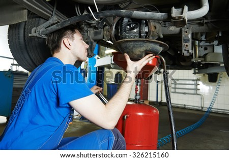 auto repairman mechanic works with rear axle reduction gear of commercial van in car auto repair or maintenance shop service station - stock photo