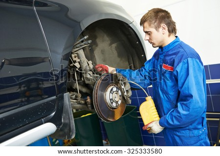 Auto service. car mechanic worker replacing brake liquid of lifted automobile at repair garage shop station - stock photo