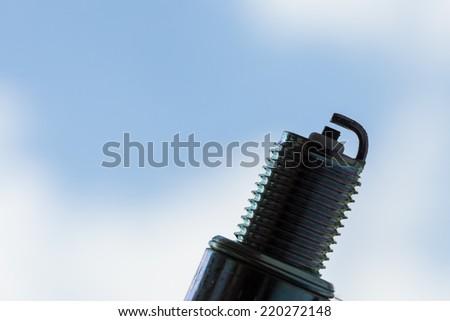 Auto service. New car spark plug as spare part of auto transportation on blue sky background. - stock photo