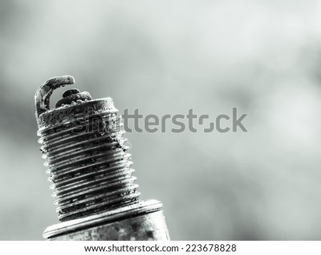 Auto service. Old car spark plug as spare part of auto transportation on blurry gray background. - stock photo