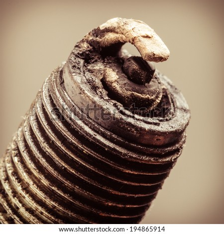 Auto service. Old rusty spark plug as spare part of car transportation on gray. - stock photo