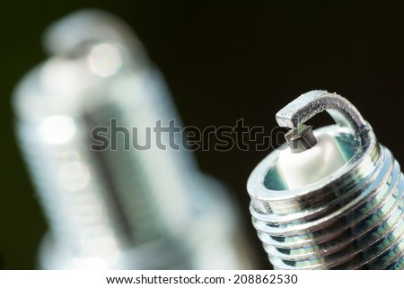 Auto service. Two new car spark plugs as spare part of auto transportation on black background. - stock photo