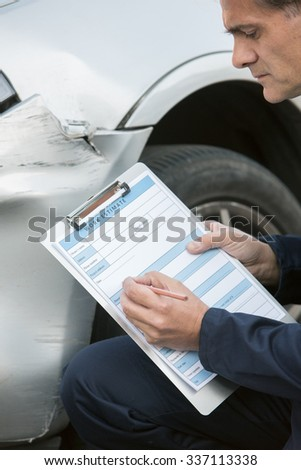 Auto Workshop Mechanic Inspecting Damage To Car And Filling In Repair Estimate - stock photo