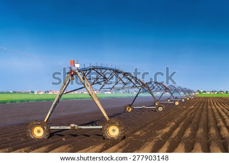 Automated Farming Irrigation Sprinklers System in Operation on Cultivated Agricultural Field on a Bright Sunny Summer Day - stock photo