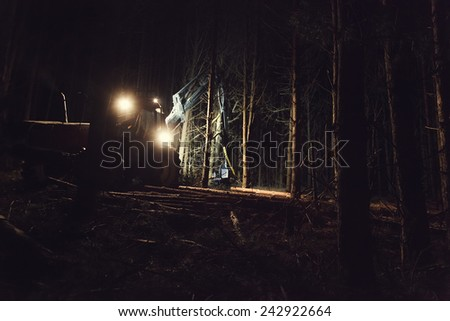 Automated felling forest at night with the help of a harvester closeup