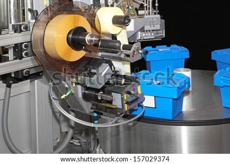 Automated labeling and packing machine in factory - stock photo