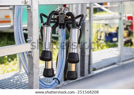 Automated mechanized milking equipment closeup for farmland industry - stock photo