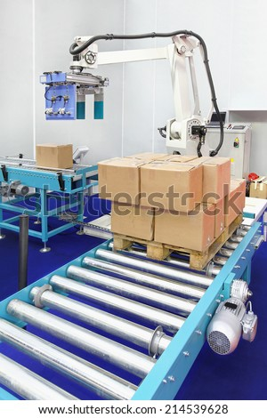 Automated robotic palletizer for boxes at conveyor rollers - stock photo