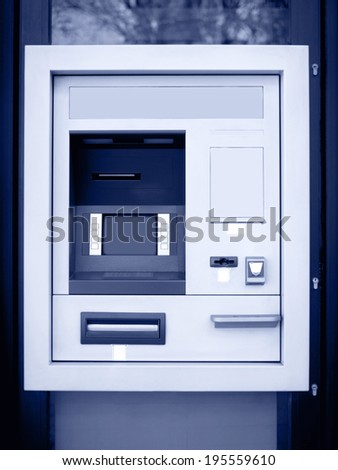 Automated teller machine in blue tone. Vertical format - stock photo