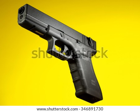 automatic hand gun on yellow background, loaded position - stock photo