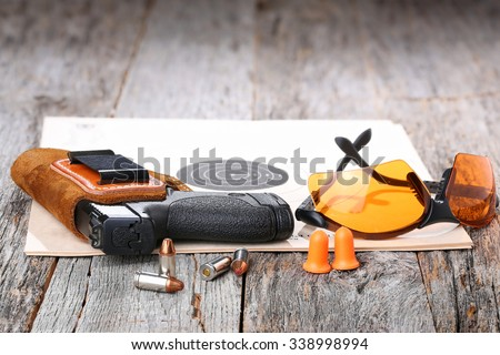 Automatic Handgun with leather holster, bullets and safety glasses on a wooden background. - stock photo
