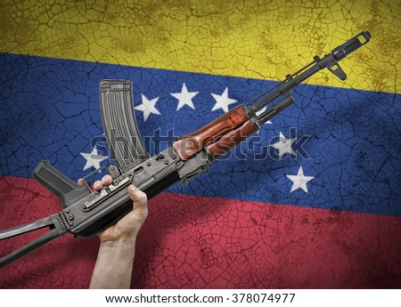 Automatic rifle in hand on background of the Venezuelan flag