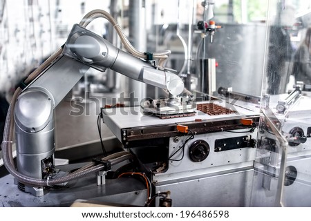 automatic robotic hand moving and preparing tiny bits of chocolate at chocolate factory.  - stock photo