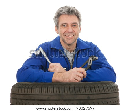 Automechanic leaning on car tires. Isolated on white