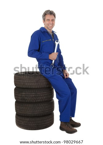Automechanic sitting on car tires. Isolated on white