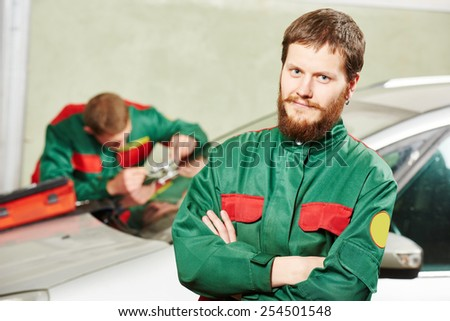 Automobile glazier repairman portrait in front of worker repairing car windscreen in auto service station garage - stock photo