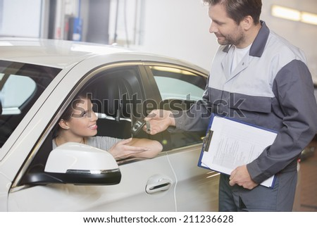 Automobile mechanic giving car key to female customer in workshop - stock photo