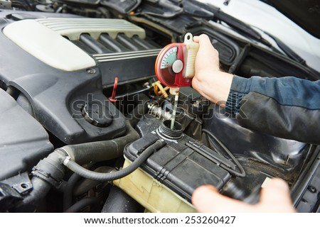 automobile mechanic tests car antifreeze liquid for winter and summer