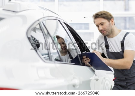 Automobile mechanic writing on clipboard while examining car in repair shop - stock photo
