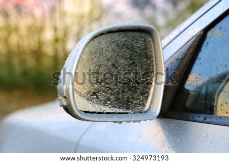 Automobile rear-view mirror in water drops after rain