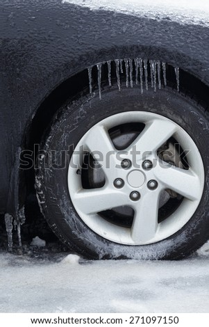 Automobile wheel and tire covered in ice from a winter storm