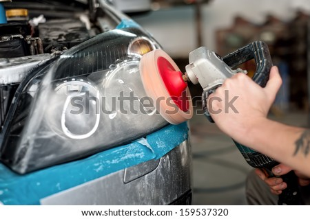 Automotive engineer polishing the headlight of a car at automobile repair and renew service station, using a professional power buffer machine - stock photo